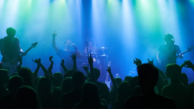 blue lights on a stage with a band singing and a crowd with their hands up