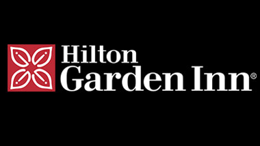 "The words ""Hilton Garden Inn"" in white on a black background next to a red and white flower icon."