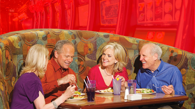Two older couples enjoy a meal at the Epic Buffet.